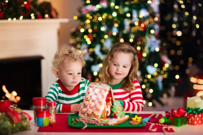 Kids making Christmas ginger bread house in decorated living room